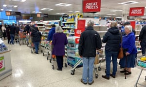 People queue inside a Sainsbury's supermarket in Watford on 19 March.