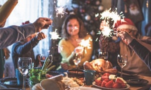 Family sitting at a table with food and wine, celebrating Christmas