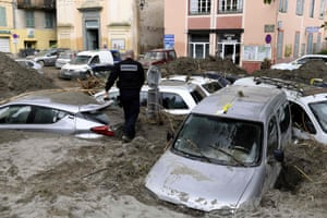 A police officer walks amongst vehicles submerged in mud in Breil-sur-Roya
