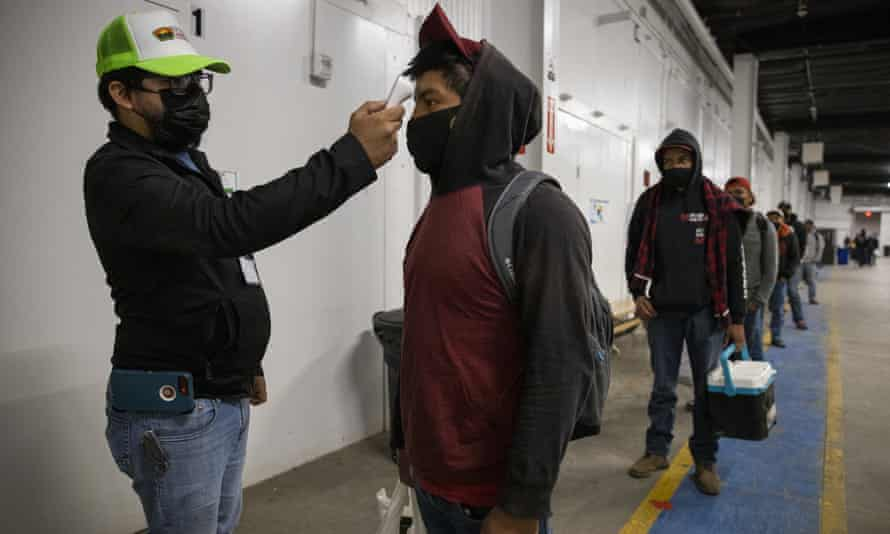 Migrant farm workers have their temperature checked before boarding the bus to their shift, 28 April 2020, in King City, California.
