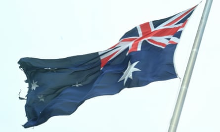 A torn Australian flag is seen on top of Parliament House in Canberra