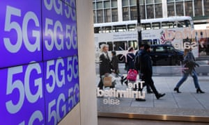 People pass a mobile phone shop in London advertising 5G