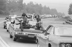 On the Road to Woodstock: A couple play the guitar sitting on their car on the way to the Woodstock Festival, August 1969.