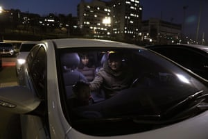 A family seen through their car windscreen. Drive-ins are popular as people can feel as though they are mixing with others, yet remain within their own cars and family units.