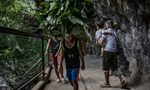 Remy Fernandez, carrying grandchild RJ, makes way for porter carrying lotus leaves to town market below, on her hour-long climb up a mountain trail to where she can buy produce directly from farmers to sell at a higher rate of profit.