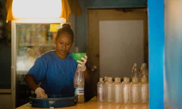 A staff member at Blue Galaxy nakamal, a kava bar in Port Vila, Vanuatu, fills plastic bottles with kava, due to Vanuatu's Covid-19 restrictions.