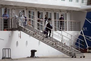 A passenger disembarks the Greg Mortimer along with others to head to the airport in Montevideo, Uruguay, on 15 April.