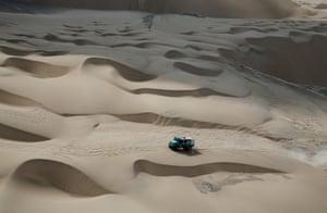 A car drives across the desert in Peru as part of the Dakar Rally