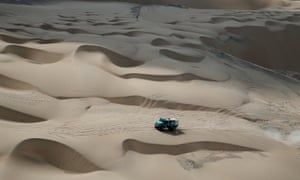 Truck driving across sand dunes in Dakar Rally