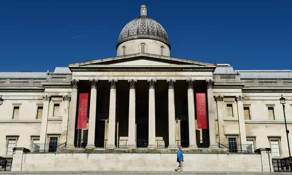 A man in a face mask walks past the deserted National Gallery, London