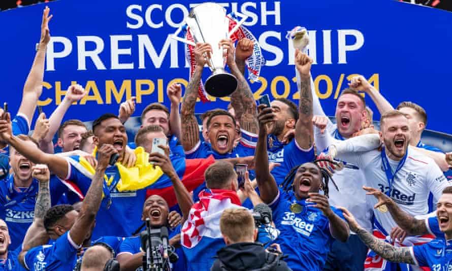 Rangers captain James Tavernier celebrates lifting the Scottish Premiership trophy alongside his teammates, management and backroom staff at Ibrox