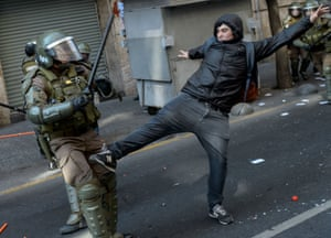 A demonstrator kicks out at a riot police officer in Santiago, Chile