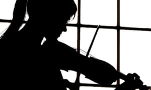 A musician playing the violin in silhouette.