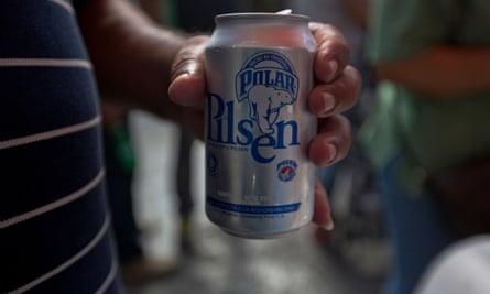 A customer drinks a Polar beer in downtown Caracas.