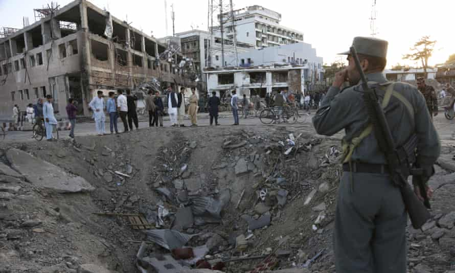 Security forces stand next to a crater created by massive explosion in Kabul in May 2017.