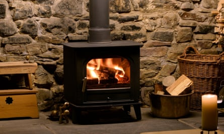 Roaring fir in wood burning stove in fireplace with logs and tongs