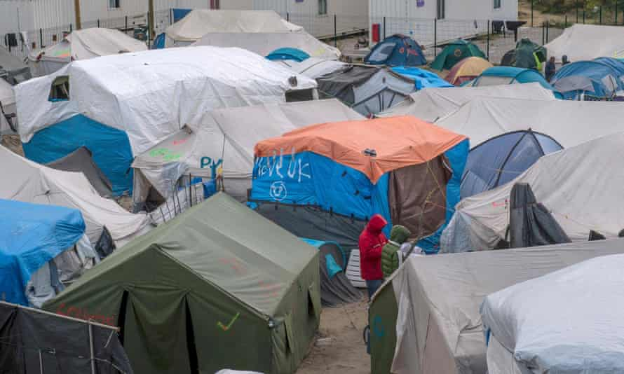 Men stand among tents at the main refugee camp in Calais.