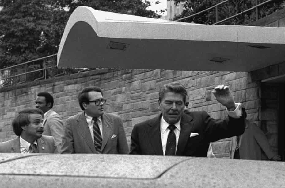 US President Ronald Reagan winces and raises his left arm as he is shot outside the Washington Hilton on 30 March 1981.