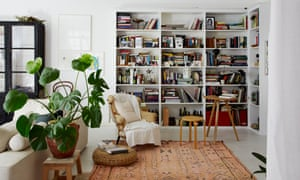 The book-lined sitting room with a large faded rug.
