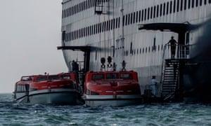 Passengers of Holland America's cruise ship Zaandam are transferred to the Rotterdam cruise ship in Panama City bay on 28 March,2020.
