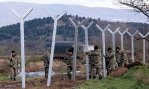 Macedonian soldiers build a metal fence at the Greek-Macedonian border, with the aim of controlling the flow of migrants through the Balkans.