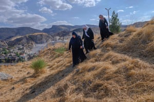 Hacire Yalcin, 55-years-old walks with her sister and her sister in-law (R) in the middle of old Hasankeyf cemetery as they search for one of their relatives' graves which will be moved to the new Hasankeyf cemetery
