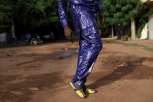 Bazin designer Baba Sereme  in a purple bazin outfit, posing in front of his home in Bamako