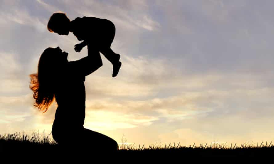 Silhouette of happy mother playing outside with a child