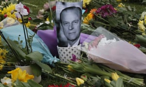 A photo of Britain's Prince Philip is among flowers left by the public outside the gates of Windsor Castle in Windsor, England.