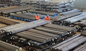 Workers check steel products at a factory in Dalian, China