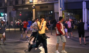 Football fans of differing nationalities and innocent bystanders try to escape tear gas fired by French police in Lille city centre.
