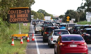 cars backed up on the highway with a sign saying covid-19 qld border contrl
