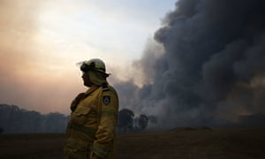 A firefighter talks on a radio as an out of control fire burns at Avery's lane, near Stanford Merthyr, east of Cessnock on Tuesday.