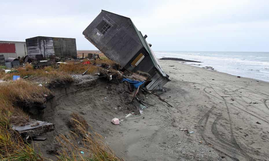 A home destroyed by beach erosion in Shishmaref tips over.