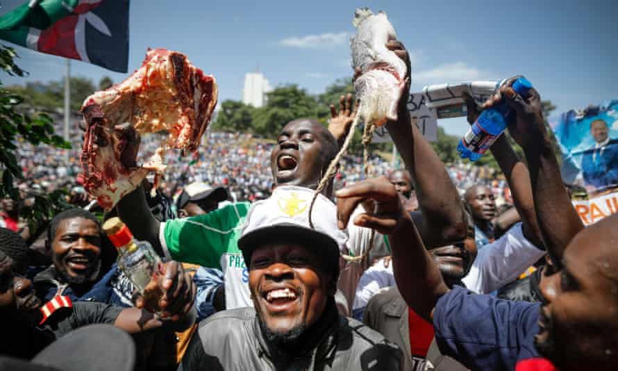 A supporter of Raila Odinga holds up a piece of meat and fish during the 'swearing-in' ceremony in Nairobi.