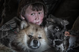 A Nenet kid poses with his animals at a nomad camp at 150 km from the town of Salekhard, Yamalo-Nenets Autonomous Okrug