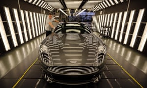 An Aston Martin Vanquish is inspected by hand inside a light booth at the company's headquarters and production plant in Gaydon.