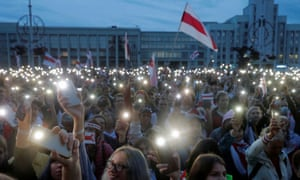 A large crowd holding up phones with the torch function illuminated, with a white and red Belarusian flag in the background.