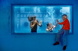 A boy staying at Butlin's watches swimmers through a window on to the pool
