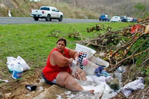 Iris Vazquez washes clothes next to a road in Corozal, west of San Juan
