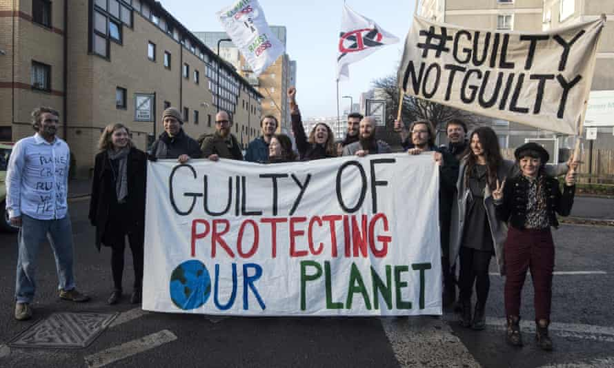 Defendants pose behind a banner outside Ealing Magistrates Court before appearing on a charge of wilful obstruction after blocking a road near Heathrow Airport in protest at climate change.