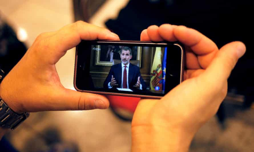 A man in Barcelona holds a mobile phone as he watches Spanish King Felipe making a televised address to the nation.