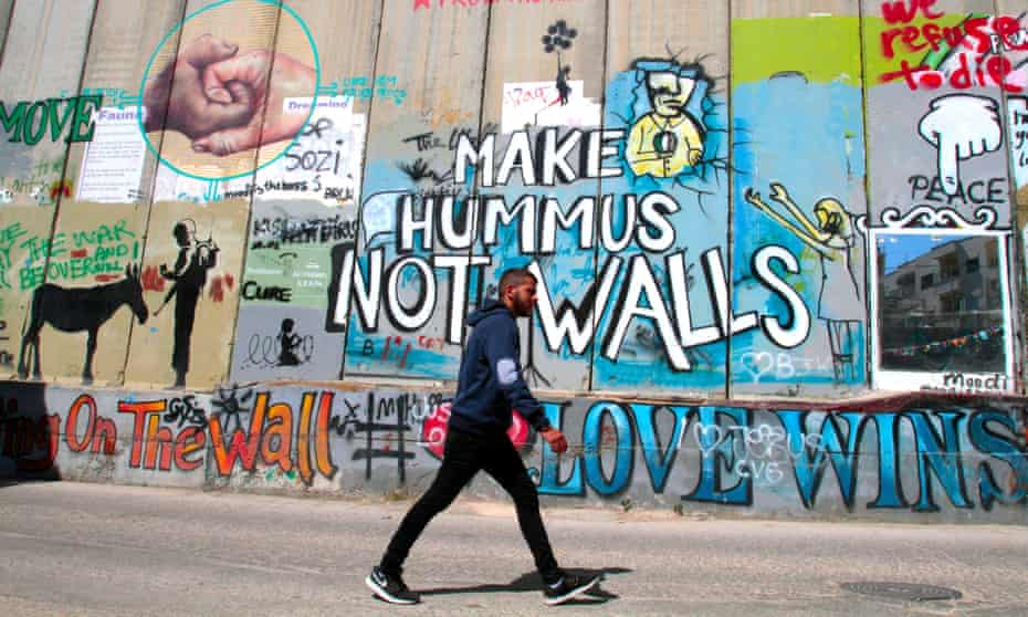 A Palestinian walks past the separating wall in Bethlehem.