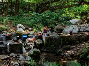 A local washes clothes at the Sant Antonio river which is drying out due to less rain falling an effect of climate change, extracting its water, the river has a long history of being used to wash clothes, bathe and even drink water since there is a spring at this area of the river.