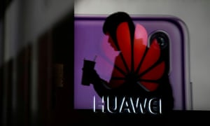 A man walking past a Huawei P20 smartphone advertisement