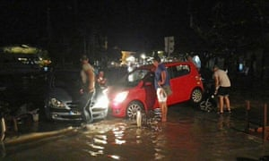 People try to move cars from a flooded coastal road in Kos