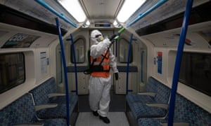 A TfL worker sprays antiviral solution inside a tube train.
