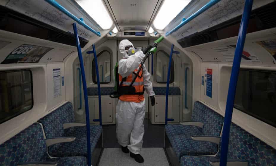 A TfL worker sprays antiviral solution inside a tube train.