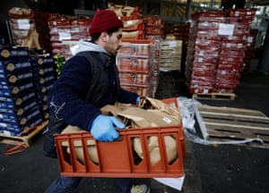 A worker at Borough Market in London, UK, carries fruit and vegetables for delivery to frontline workers at three NHS hospitals
