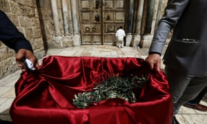 A man prays in front of the closed doors of the Church of the Holy Sepulchre as members of Latin Patriarchate prepare to distribute olive branches to Christian residents on Palm Sunday, during Holy Week amid the coronavirus outbreak in Jerusalem's Old City.